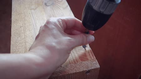 Female hands tighten the screw with a drill. The concept of boundaries of traditional gender roles.