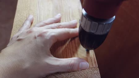 Female hands unwind the screw with a drill. The concept of the boundaries of traditional gender roles.
