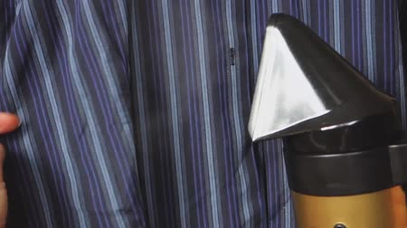 A young girl strokes a blue, striped, mens shirt with a steam iron.