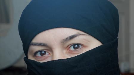 Portrait of a beautiful arab girl. An Islamic woman in a hijab looks into the camera. Vídeos