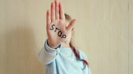 Concept of domestic violence and child abusement. A little girl shows her hand with the word STOP written on it. Children violence. Vídeos