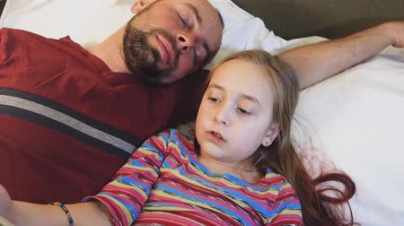 The father sleeps while the daughter reads him a fairy tale. Dad fell asleep while reading a book. Vídeos