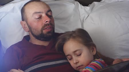 Father reads a bedtime story to his daughter. The daughter sleeps hugging her father, who reads her book. Vídeos