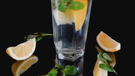 Sparkling cocktail with slices of lemon, ice cubes and mint on a dark background.