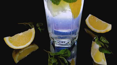 Sparkling cocktail with slices of lemon, ice cubes and mint on a dark background Vídeos