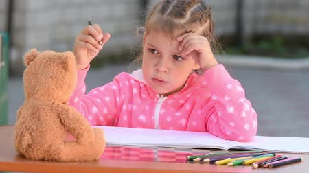 incapacidade : Five-year girl thought, sighed, and went on to draw a teddy bear