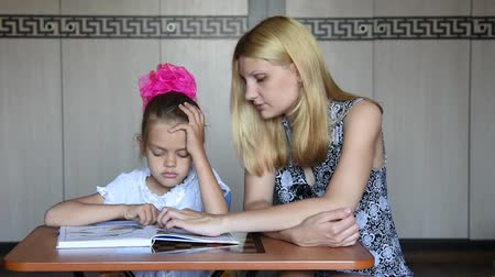 учение : Tutor girl explains the meaning of the task in the textbook Стоковые видеозаписи