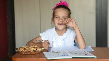 finomságok : Seven-year girl schoolgirl doing homework snacking biscuits