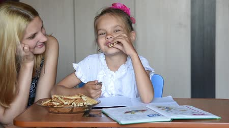 snack : Seven-year school girl eating homemade liver tells mom about homework