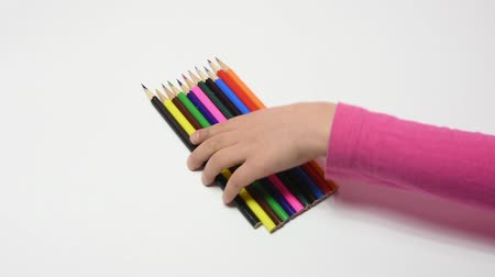 took : Childrens hand has collected a set of colored pencils