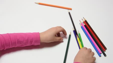 took : Childs hand turned the pencils in their hands and collected the whole set of pencils Stock Footage