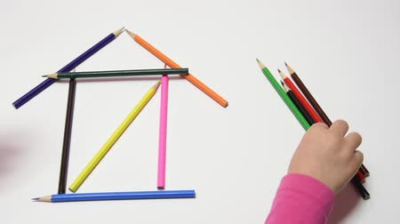 improvised : Children hand construct house from pencils on a sheet of paper