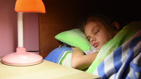leisure time : Mans hand turned out the light from a table lamp in crib fallen asleep girl Stock Footage