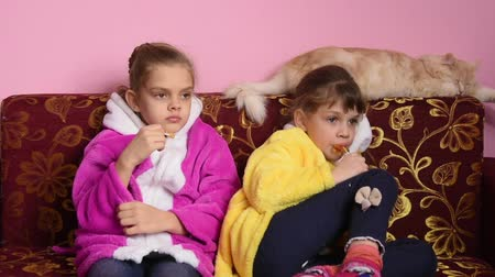 guloseimas : Two girls sitting on the couch and watching TV enthusiastically