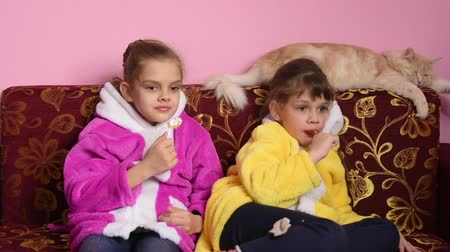 finomságok : Girls sit on the sofa, lick lollipops and watch TV, the TV suddenly turned off