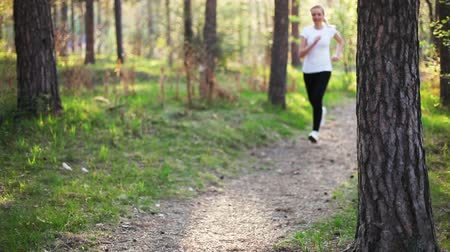 jogging : young blonde woman running in evening park