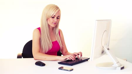 teclado : young blonde woman working and talking by mobile phone, over white background