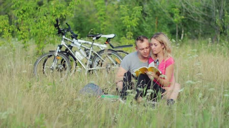 notebooklar : Attractive couple holding books and kissing during studying in the park  Stok Video