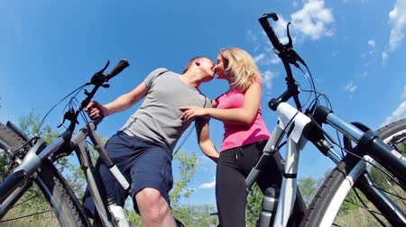 amantes : Two attractive couple holding their bikes and kissing