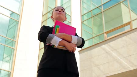 bina : Pretty student holding her copybooks near the office building