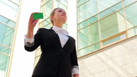 gündelik kıyafetler : Young smart businesswoman showing her card near the office building