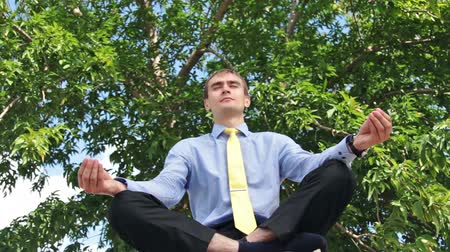 размышлять : Young businessman doing yoga in the park