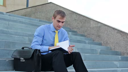 pensamento : Young serious businessman writing on notepad and standing up