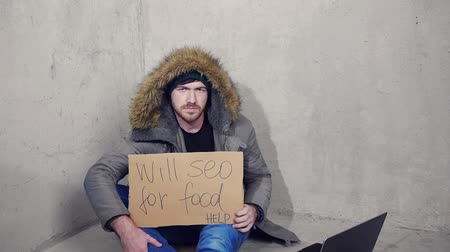 голодный : homeless man sitting on the floor with a cardboard asking for a help Стоковые видеозаписи
