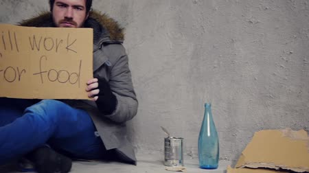hajléktalan : homeless sitting on the floor with a cardboard and a tin