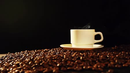 bögre : cup of black hot coffee standing on the coffee beans