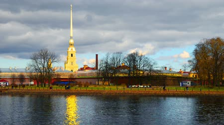st petersburg : Saint Petersburg, Russia. Unidentified people walking by the entrance to Peter and Paul fortress. Popular landmark in the city. Time-lapse with cloudy sky in autumn