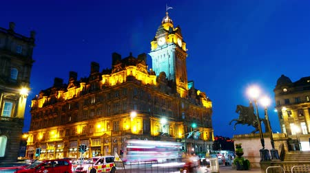 skotsko : Edinburgh, UK. Night view of Edinburgh, Scotland with illuminated Balmoral Hotel and clock tower. Time-lapse of car traffic trail lights with blue sky Dostupné videozáznamy