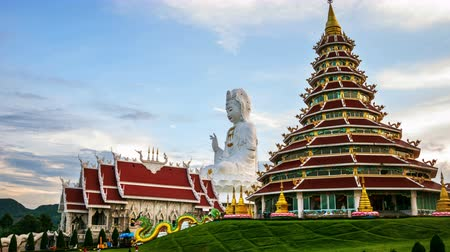 huai : Chiang Rai, Thailand. Wat Huai Pla Kung Temple at sunset in Chinag Rai, Thailand. Illuminated Buddha statue and temple with cloudy blue sky. Time-lapse at sunset Stock Footage