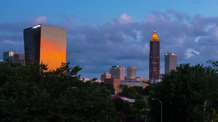 ga : Atlanta, USA. Time-lapse of Midtown in Atlanta, USA night to day. Fast pacing clouds over the skyscrapers in the morning. Zoom out Stock Footage