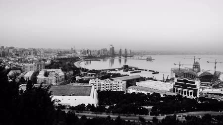 baku : Aerial view of Baku, Azerbaijan from evening to night. Coastline of the capital of Azerbaijan with cloudless sky. Time-lapse Port of Baku with historical buildings. Black and white Stock Footage