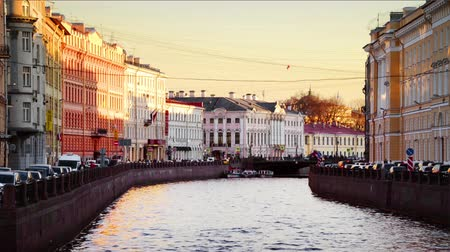 st petersburg : St Petersburg, Russia. Moyka river in Saint Petersburg, Russia in the evening, historical buildings, bridges and clear sunset sky. Various bars and restaurants. Time-lapse of touristic boats Stock Footage