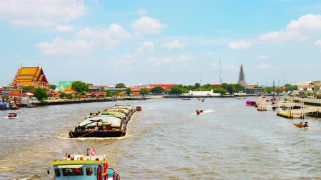 chao : Bangkok, Thailand. River traffic in Bangkok, Thailand during a day with partial clouds. Various temples, blue sky