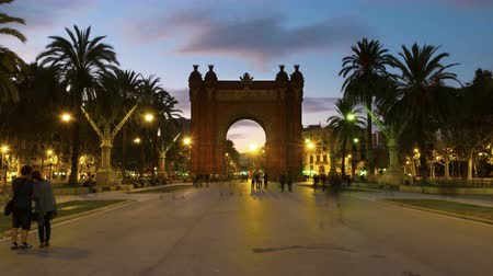 triumphal arch : Barcelona, Spain. Arch of Triumph in Barcelona, Spain at night. Time-lapse of a sunset, motion blurred people, lights and illumination