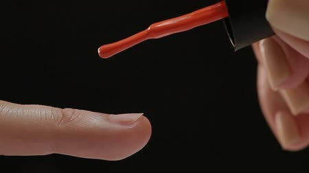unha : Beautiful manicure process. Nail polish being applied to hand, polish is a red color. Black background closeup. Stock Footage
