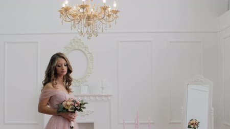 kıvırcık saçlar : Beautiful brunette girl with bouquet of flowers in pink wedding dress in classic hall Stok Video