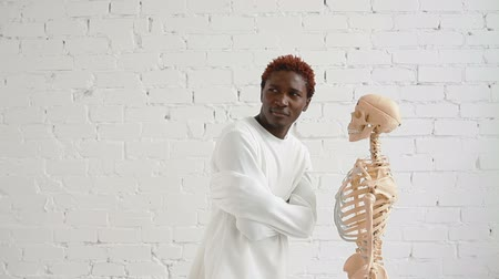garip : An insane black man wearing a straitjacket dance and looking at human skeleton stand Stok Video