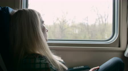 utazó : Young caucasian Woman look thru the window while traveling by train