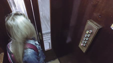 lower part : Young woman with backpack press level button in old working cage elevator and move downward