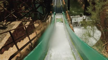 rolete : Point of view - Fun wet roller coaster boat going down the hill into a splashing pool of water