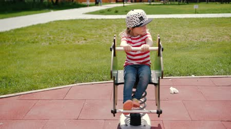 подача : little child girl play in a park sit on swing Стоковые видеозаписи