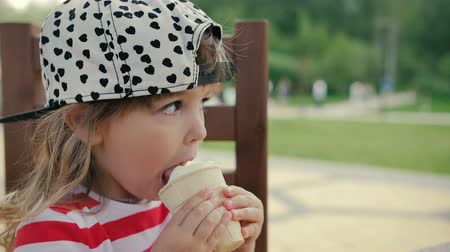 dondurma : Little girl sits on the chair and eats ice cream Stok Video