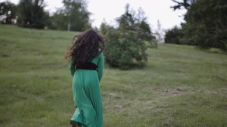 látszó el : young brunette woman with long hair happily running away on warm summer day. Pretty woman dressed in green dress enjoying nature outside.
