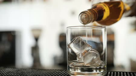 kocka : Whisky is poured over ice in slow motion