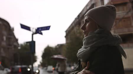 deep autumn : depressed young woman looks at the street on a rainy evening in the town