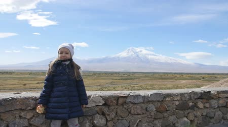 viewpoint : Portrait of vacation travel little girl looking at Ararat mountain landscape. Nature during summer vacations. Young kid standing at lookout looking at camera.